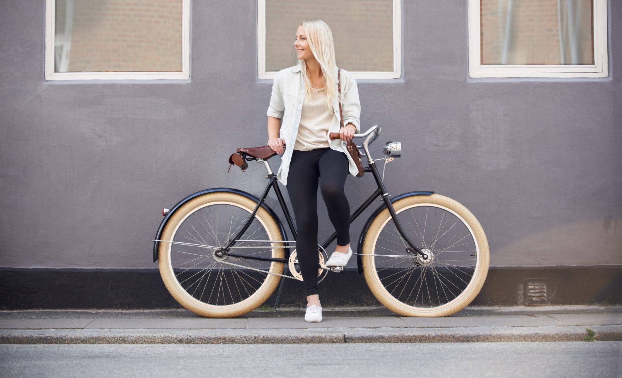 Dziewczyna stojąca przy rowerze z jasnymi oponowami opartym przy ścianie