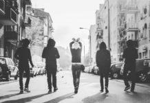 Czarno-biale zdjęcie przedstawiające cztery osoby idące tyłem do ulicy