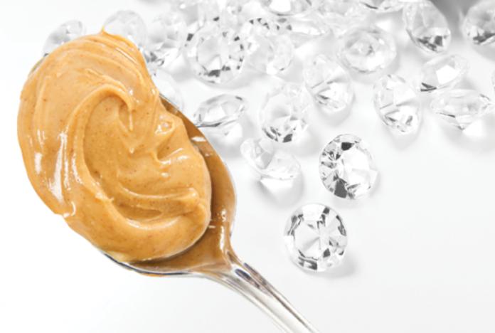 Łyżka z masłem orzechowym, obok diamenty