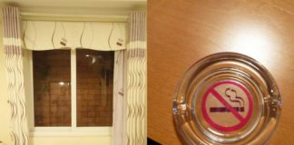 Okno za którym widać ścianę z cegieł i popielniczka z zakazem palenia
