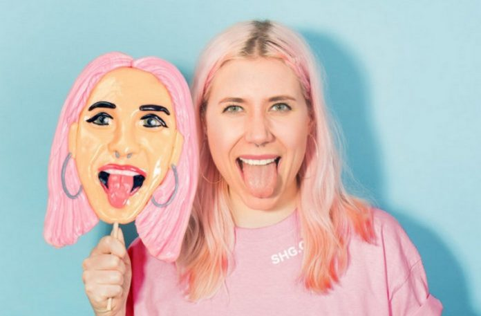 Dziewczyna z różowymi włosami, stojąca z lizakiem przedstawiajacym jej twarz
