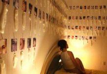 Dziewczyna siedząca na łóżku, dookoła na ścianach zużyte prezerwatywy