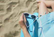 Ręka trzymające okulary, na zdjęciu widoczny jest też fragment niebieskiej sukienki