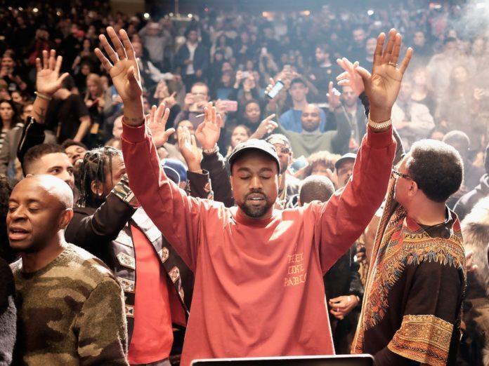 Ciemnoskóry mężczyzna w koralowej bluzie i czapce z daszkiem z uniesionymi rękami i zamkniętymi oczami na tle tłumu ludzi.