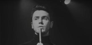 Czarno-biały kadr prezentujący mężczyznę z mikrofonem w dłoni