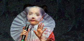 Kobieta w ekscentrycznym przebraniu z białą woalką na głowie z mikrofonem w ręce.