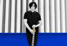 Czarno-białe zdjęcie mężczyzny z gęstymi włosami, ubranego na czarno, stojącego z gitarą