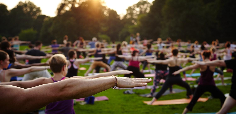 Grupa ludzi uprawiająca jogę w parku o zachodzie słońca.
