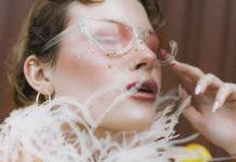 Kobieta pozująca profilem w krótkich włosach i szalu z piórek dookoła głowy