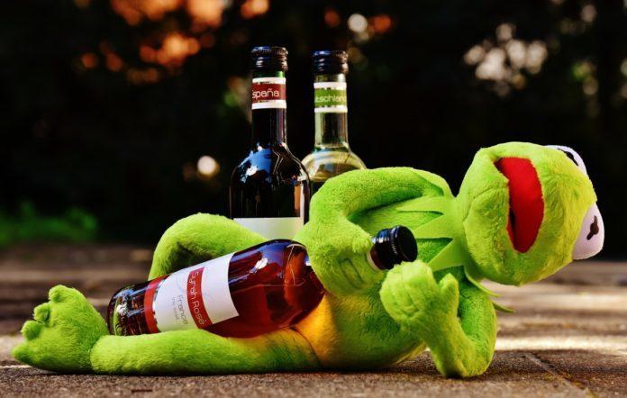 Żaba Kermit leząca z butelką w rękach