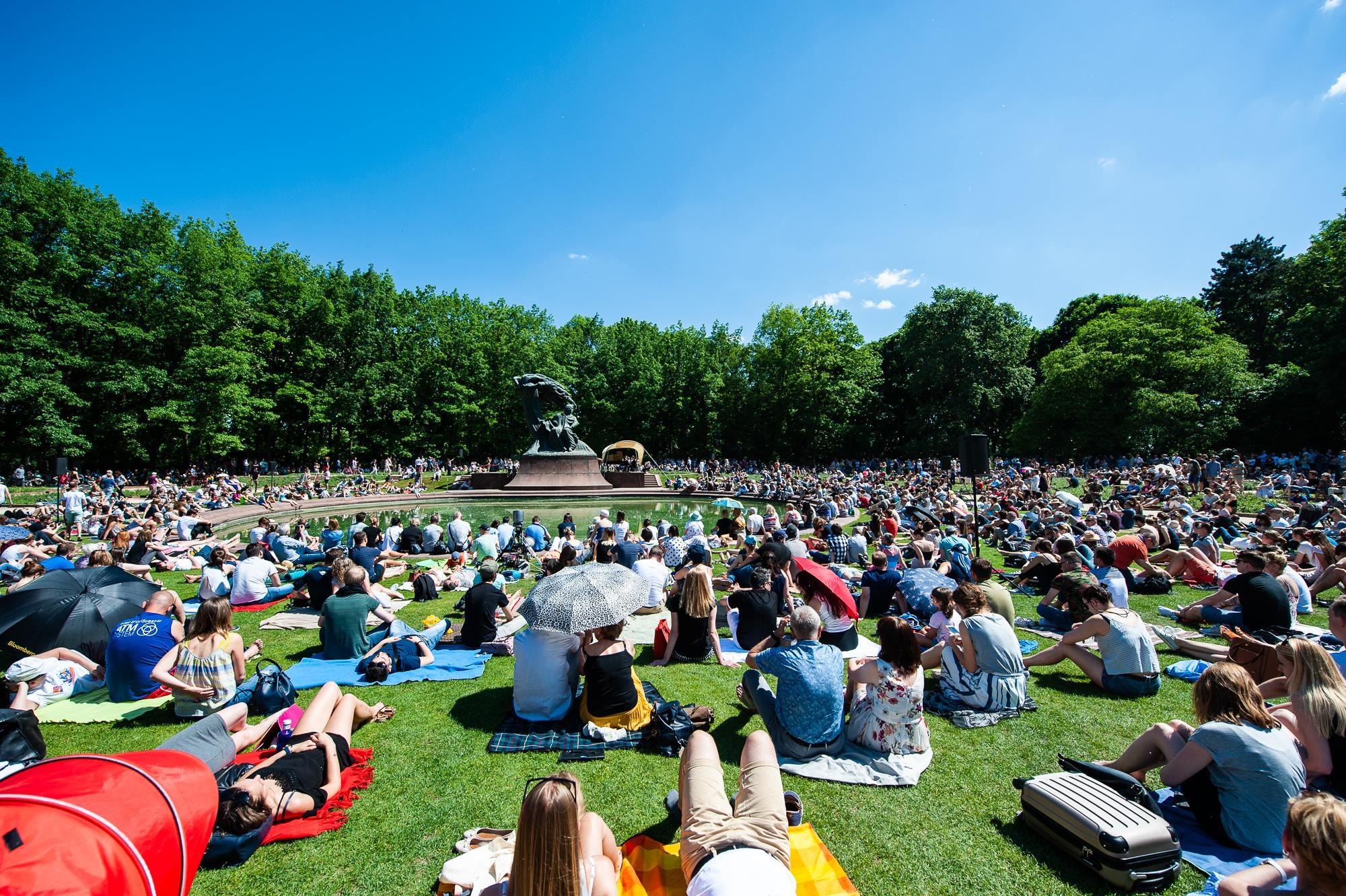 Ludzie siedzący i leżący na trawie skierowani w stronę pomnika.