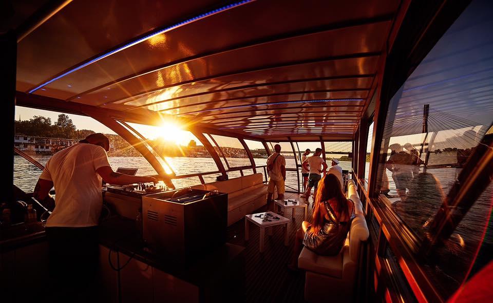 Statek rejsowy z djem i grupą osób przy zachodzącym słońcu.