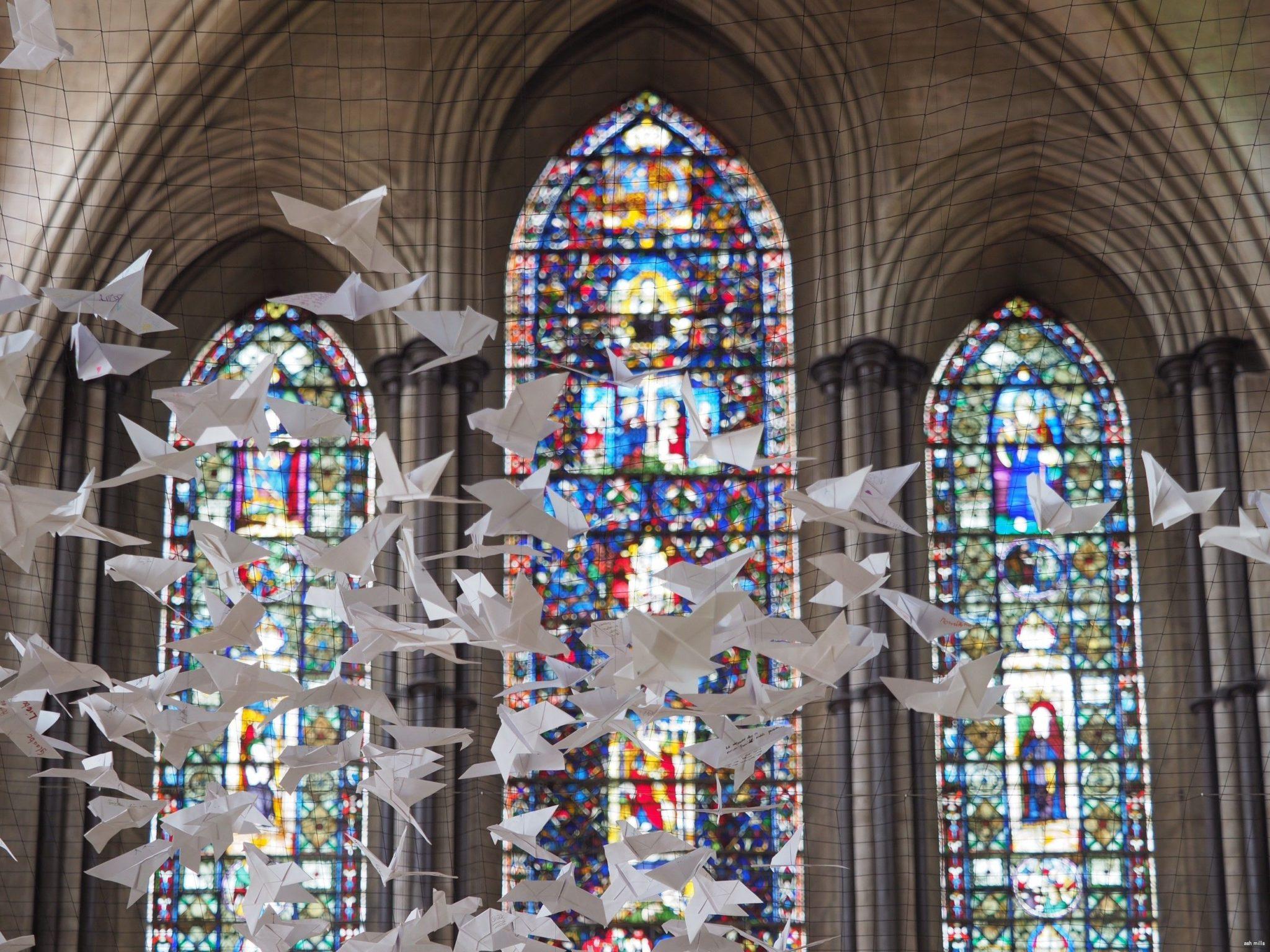 Białe papierowe gołębie zawieszone pod sklepieniem gotyckiego kościoła.
