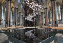 Wnętrze gotyckiej katedry wypełnione mnóstwem białych papierowych ptaków.