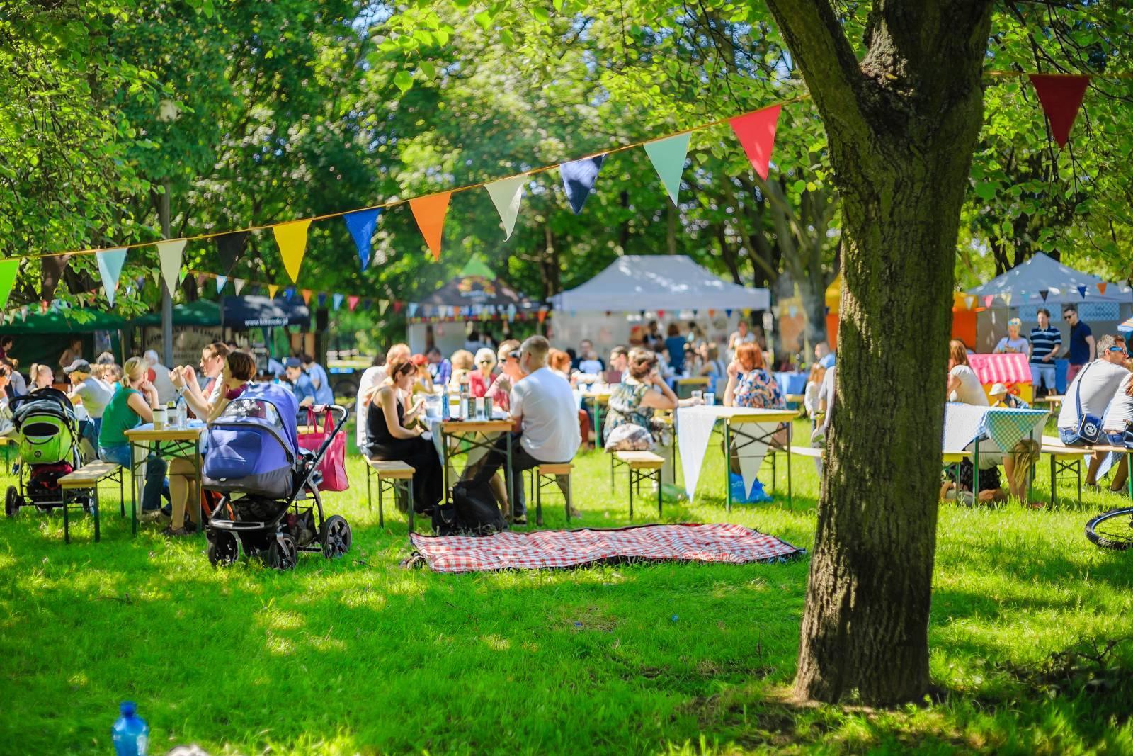 Ludzie piknikujący w parku przy stolikach, w tle namioty z jedzeniem.