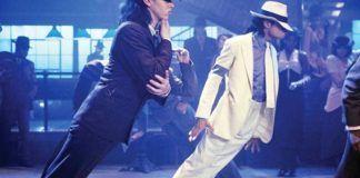 mężczyźni na scenie w białym i czarnym garniturze pochylają się do przodu.