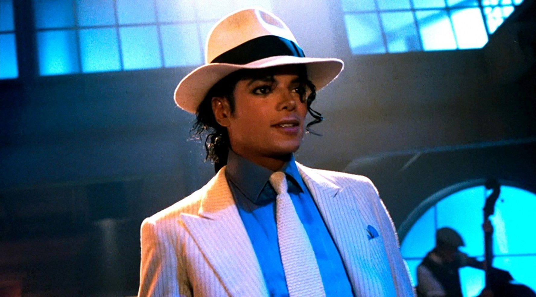 Ciemnoskóry mężczyzna z czarnymi lokami w białym kapeluszu, białym krawacie, niebieskiej koszuli i białej marynarce.