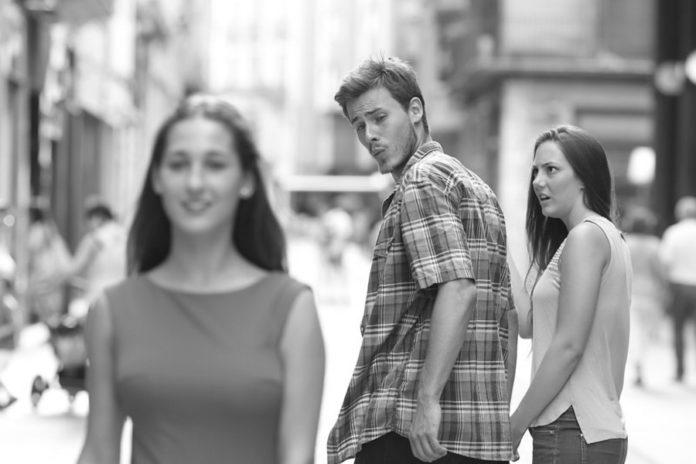 Chłopak idący z dziewczyną oglądający się za inną