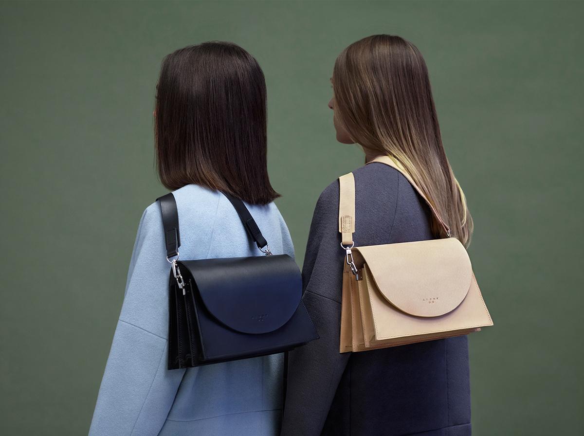 Na zdjeciu widzimy dwie dziewczyny stojace tylem na ich plecach nonszalancko zwisaja dwie torby