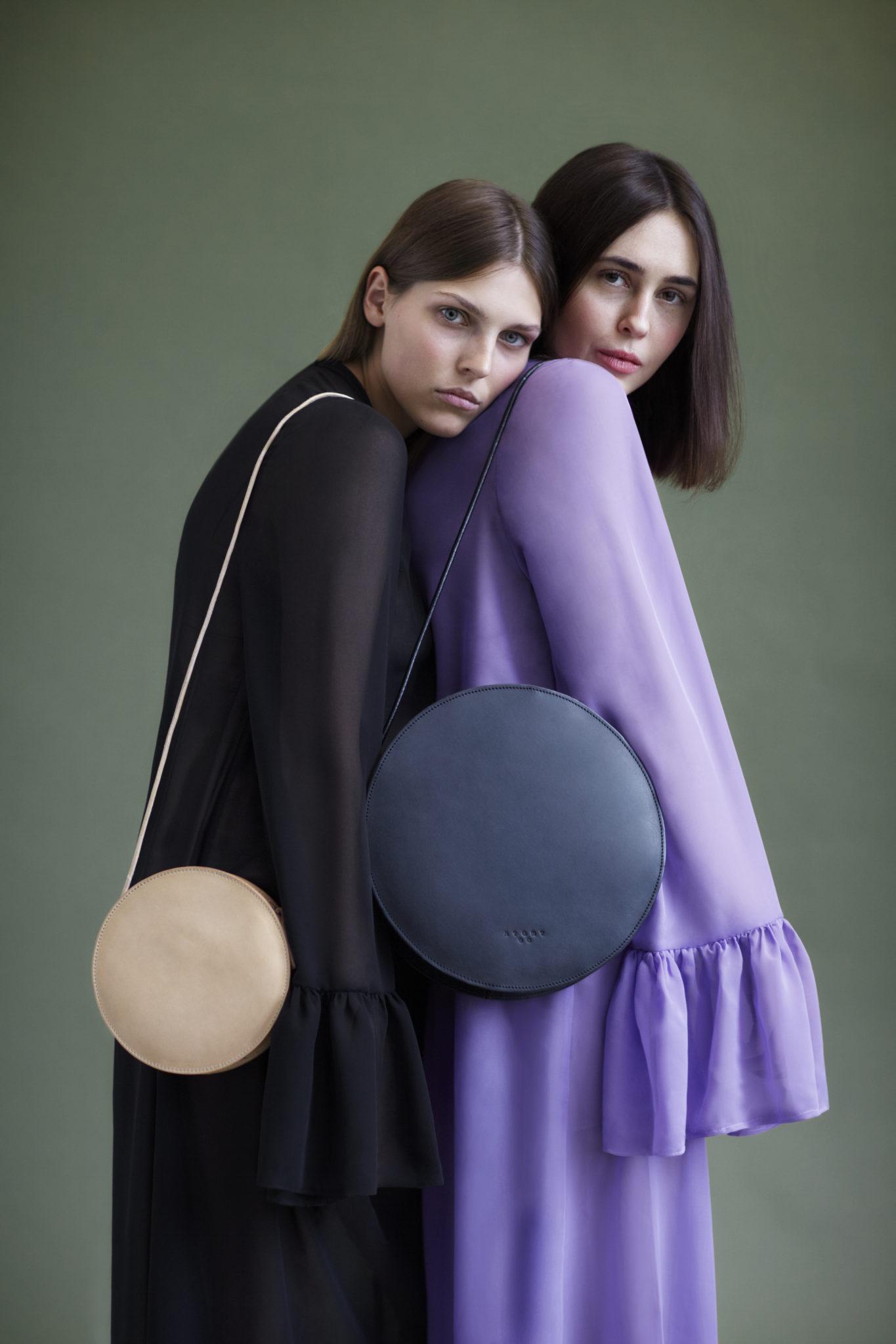 Na zdjeciu widzimy dwie dziewczyny oparte o siebie na ich ramionach wisza okragle torby
