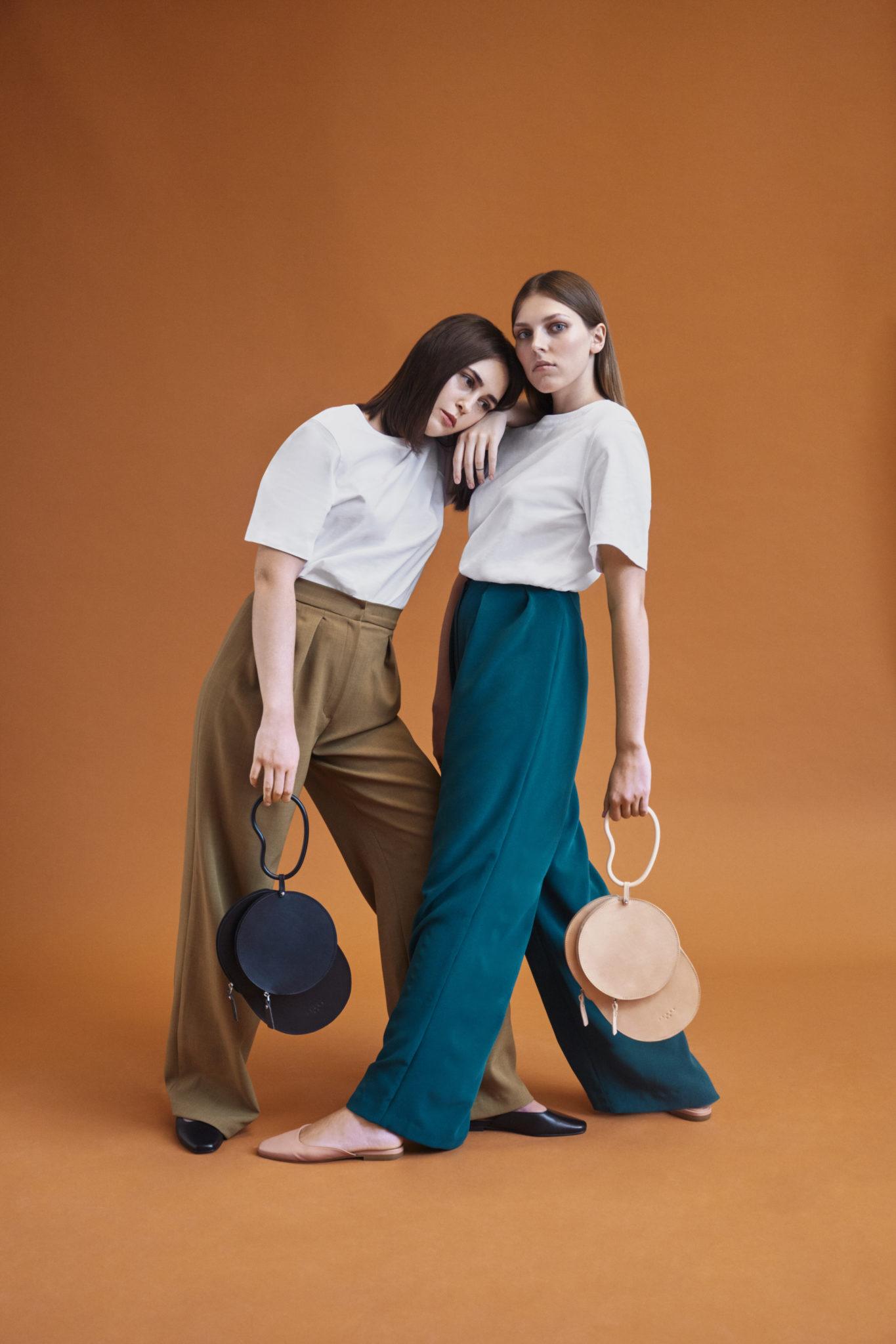 Na zdjeciu widzimy dwie dziewczyny oparte o siebie trzymajace okragle torby