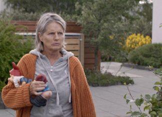 Kobieta ubrana w dres stoi przed domem i trzyma w ręku dwa krasnale ogrodowe
