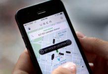 Ręka trzymająca telefon z otwartą aplikacją Uber