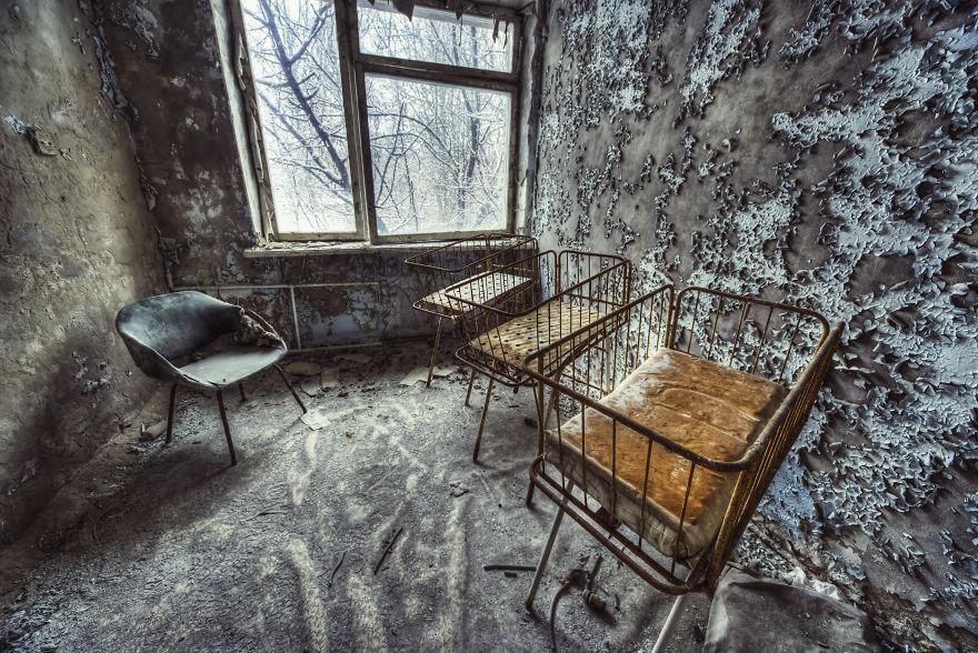 Opuszczone wnętrze budynku z dziecięcymi łózeczkami