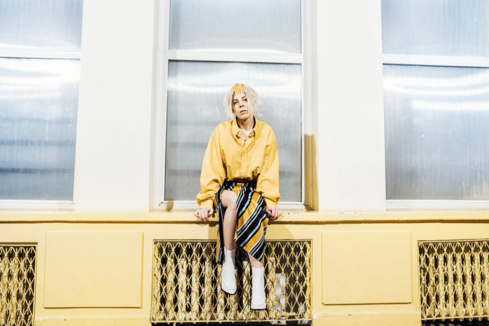Dziewczyna ubrana w żółtą bluzkę i kolorową spódnice siedzaca na parapecie