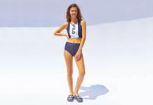 Modelka ubrana w kostium kąpielowy marki FILA w kolorze granatowym.