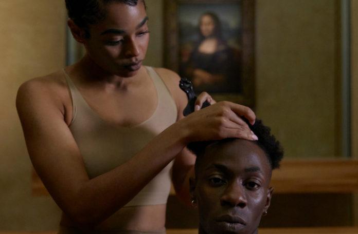 Mjulatka goląca głowę ciemnoskóremu mężczyźnie