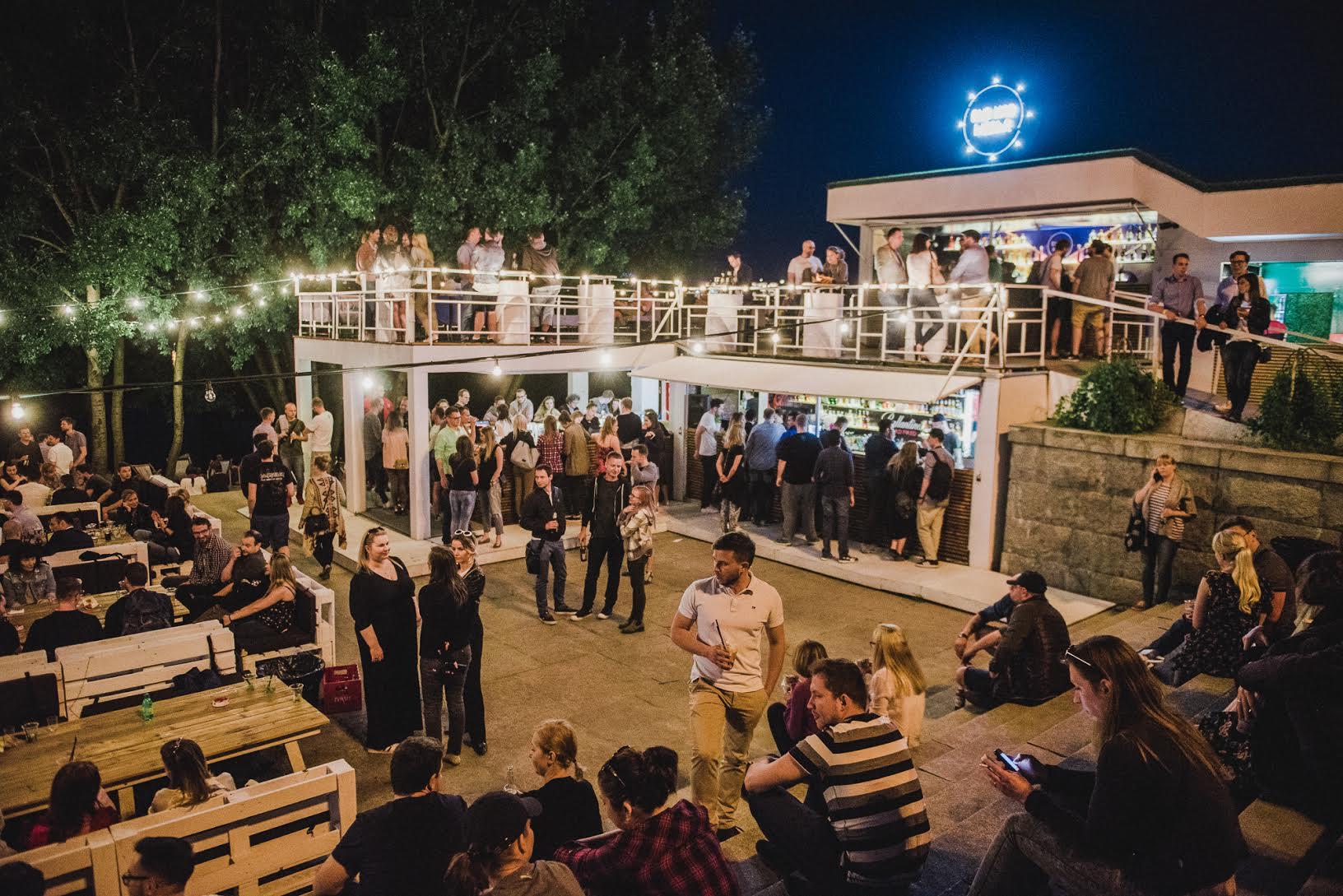 Tłum ludzi rozmawiających w grupkach, siedzących na schodach i pijących napoje przy barze na otwartym powietrzu po zmroku.