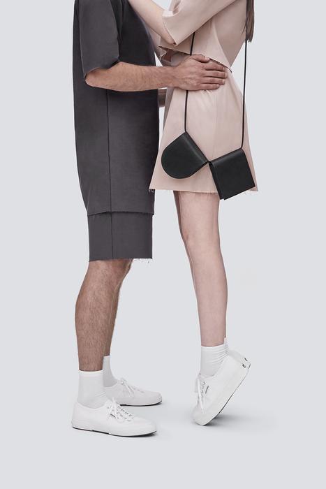 Na zdjeciu widzimy mezczyzne i kobiete od pasa w dol kobieta ma na sobie dwie torby