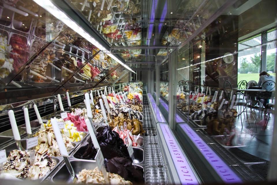 witryna z lodami widziana z profilu, po lewej stronie kubełki z lodami, po prawej w szybie obijają się krzesła i stoliki.
