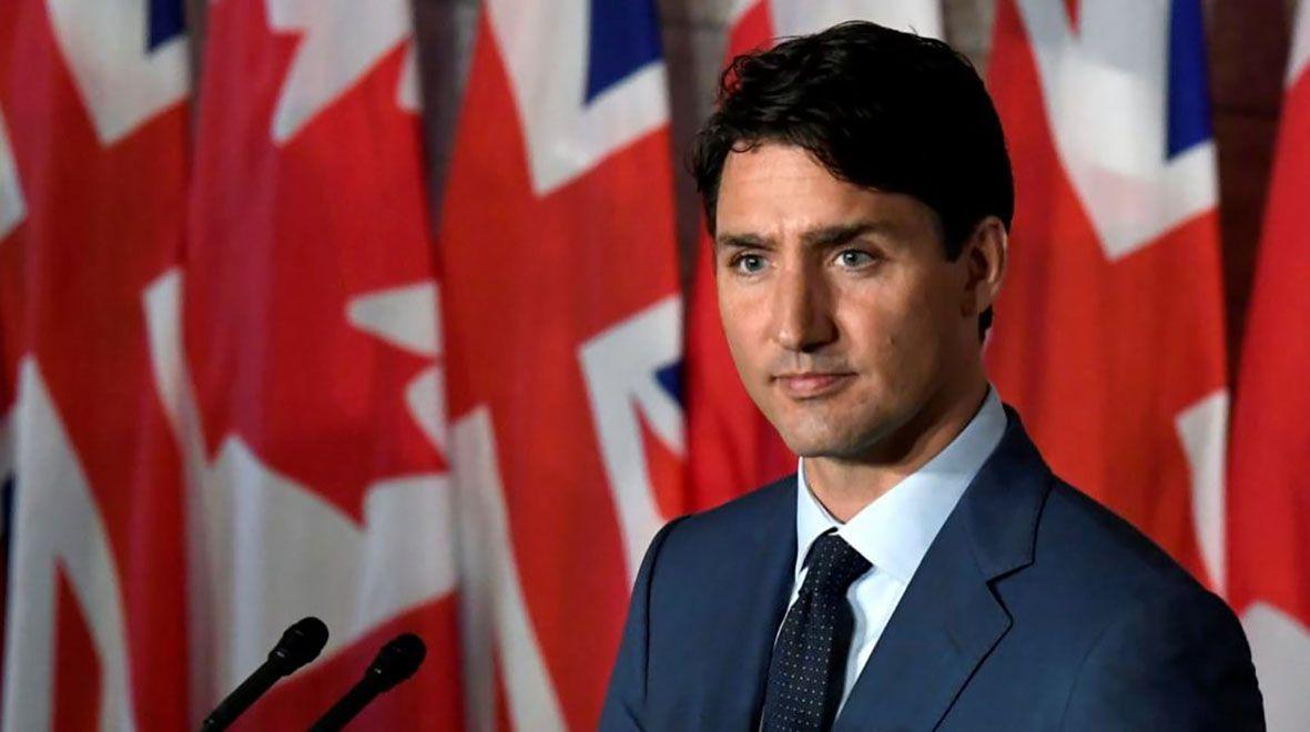 Mężczyzna ubrany w garnitur na tle flag kanady