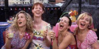 Cztery śmiejące się dziewczyny z kieliszkami w dłoniach