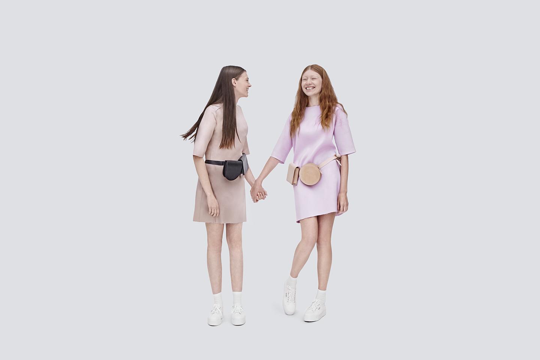 Dwie dziewczyny trzymaja sie za reke smieja sie maja na pasie torebki
