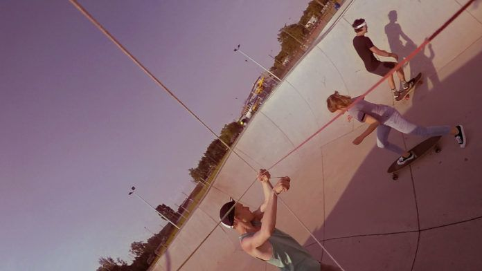 zdjecie przedstaiwa mlodych ludzi na skateparku chlopcow i jedna dziewczyne bawiacych sie w sloneczny dzien