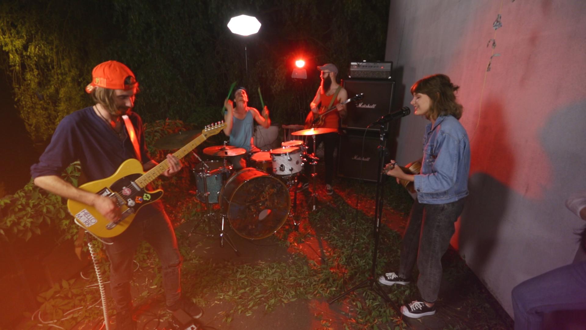 Na zdjęciu widac wieczorne jam session zespolu, w ktorym wokalistka jest dziewczyna a oswietla ich czerwone swiatlo