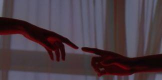Dwie wyciągnięte do siebie dłonie stykające się palcem