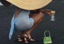 Kucająca kobieta, a obok niej miniaturowa torebka