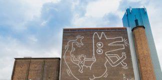 Mural postaci z głową psa na ceglanej ścianie