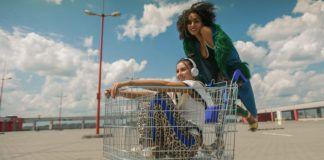 Dziewczyna siedząca w wózku sklepowym i druga ciemnoskóra dziewczyna opierająca się na jego uchwycie