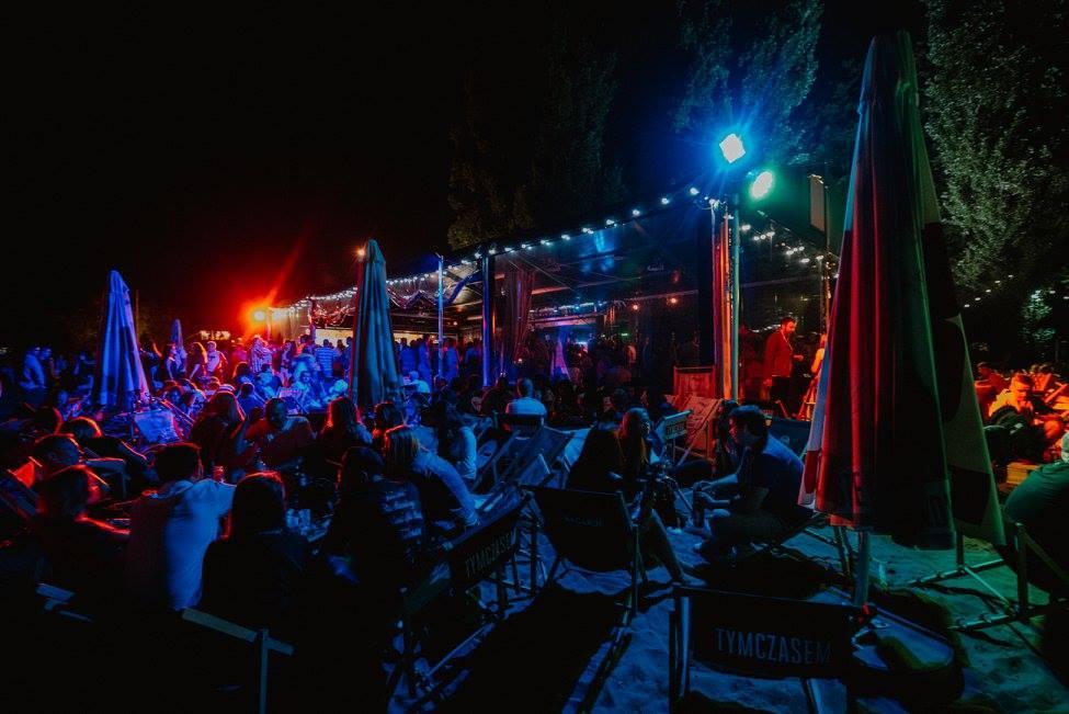 Ludzie siedzący na leżakach, pijący napoje, tańczący w barze na otwartym powietrzu po zmroku.