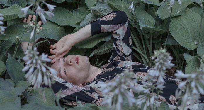 Chłopak lężący w zielenonych roślinach