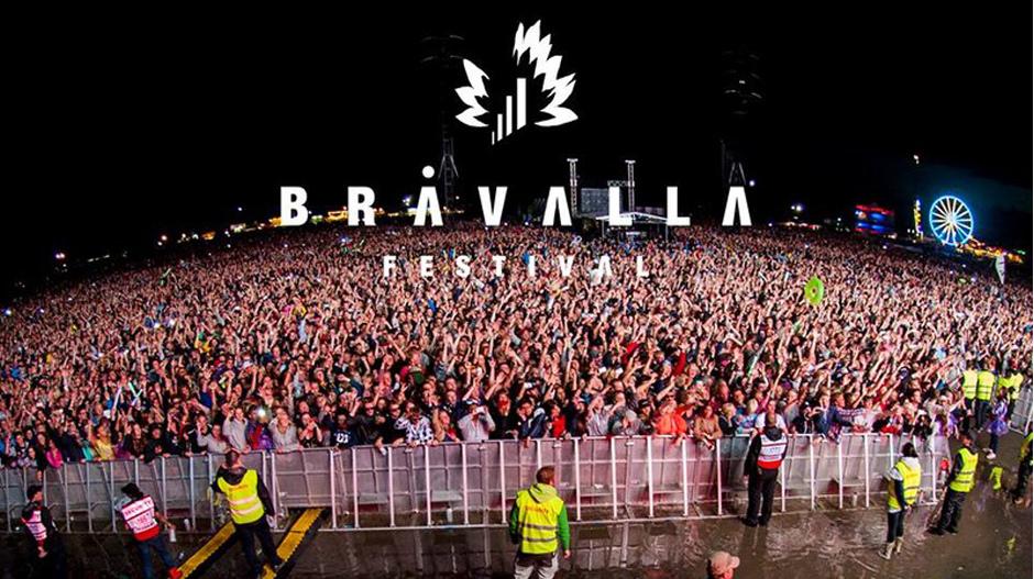 Zdjęcie publiczności na festiwalu Bråvalla w Szwecji. Ludzie odgrodzeni barierkami i kordonem ochrony.