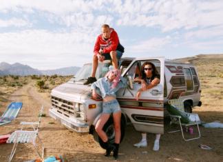 Grupa ludzi stojąca przed vanem na pustyni