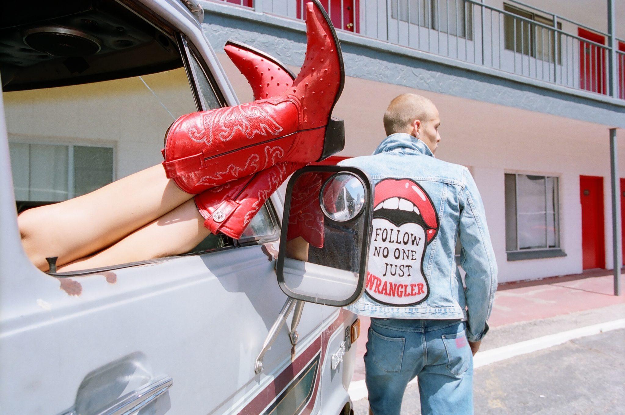 Czerwone kowbojki wystające z vana i chłopak w jeansowej kurtce z językiem