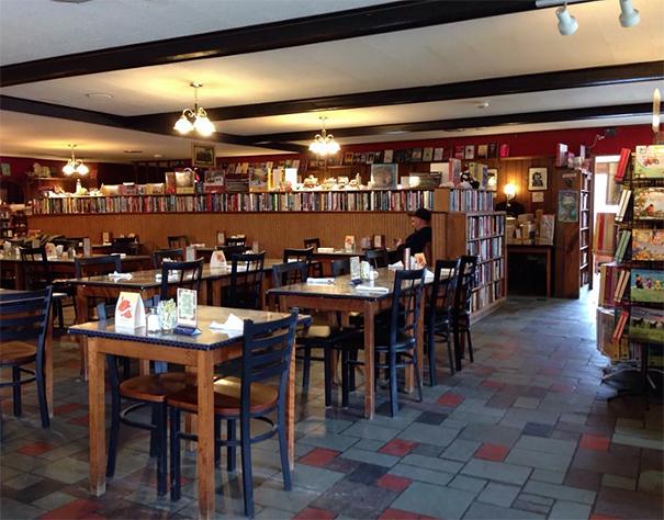 Stoliki w restauracji i półki z ksiązkami
