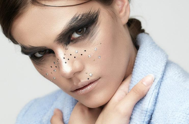 Modelka w niebieskim płaszczu z ciemno pomalowanymi oczami i brokatem na twarzy